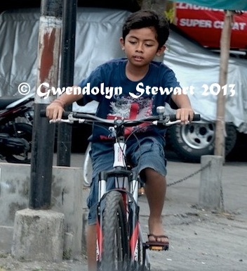 Boy Riding a Bike on Bali, Indonesia, Photographed by Gwendolyn Stewart, c. 2014; All Rights Reserved